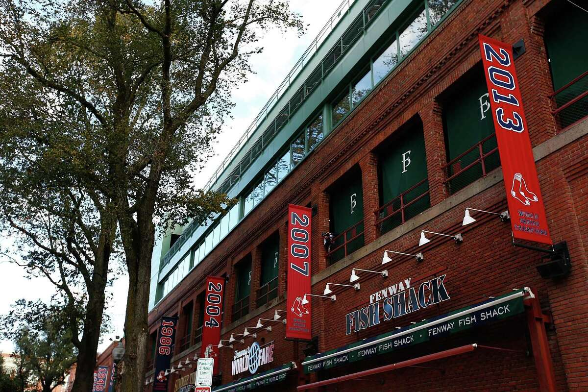Among the banners displayed outside Fenway Park are those commemorating the Red Sox's three championships between 2004 and 2013.