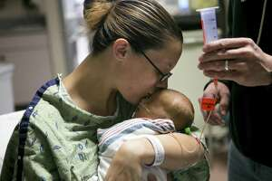 Stephanie Athey kisses her 10-day-old son Ethan in University Hospital's neo-natal intensive care unit on Sept. 6, 2018. Athey was seriously injured when a car smashed into a West Side bus stop on Aug. 28. She was rushed to University Hospital, where the medical staff saved her life and delivered Ethan.