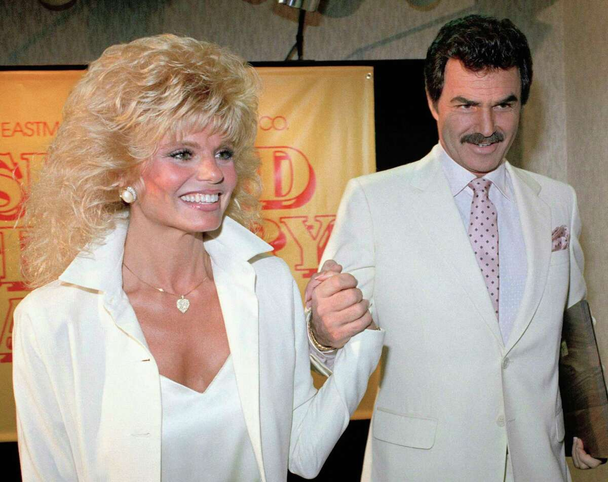 """FILE - In this March 27, 1987 file photo, Burt Reynolds, right, holds hands with Loni Anderson at luncheon in Los Angeles. Reynolds, who starred in films including """"Deliverance,"""" """"Boogie Nights,"""" and the """"Smokey and the Bandit"""" films, died at age 82, according to his agent. (AP Photo/Bob Galbraith, File)"""