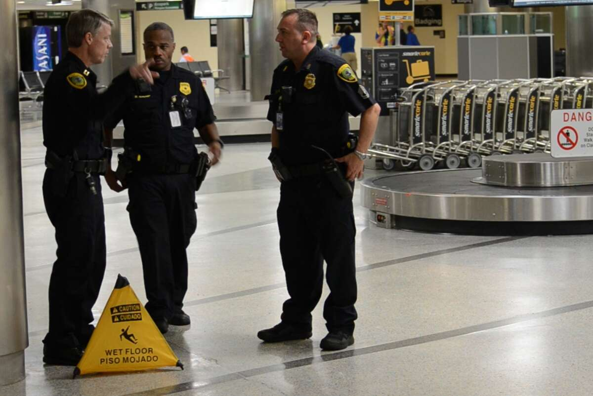 Houston police officers investigate the scene where a Houston police officer mistakenly discharged a gun inside the Hobby Airport baggage claim area Thursday, Sept. 6, 2018.