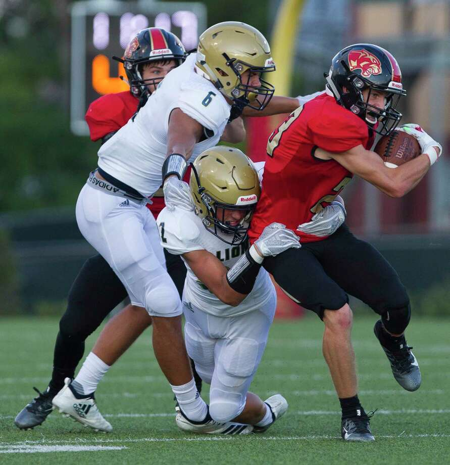 Caney Creek wide receiver Jaiden Besaw (23) is tackled by Lake Creek's Kyle Scott (32) and Ethan Harper (6) during the first quarter of a non-district high school football game at Buddy Moorhead Stadium on Friday, Aug. 31, 2018, in Conroe. Photo: Jason Fochtman, Staff Photographer / Houston Chronicle / © 2018 Houston Chronicle