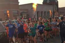 Participants take part in the 2017 Torch Run heading down Main Street in Midland.
