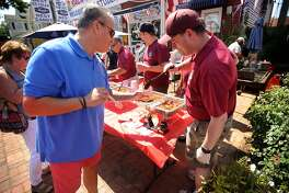 Jon Starr, left, of Norwalk, samples the chili of three time winner George Ribellino, of Norwalk, at the 4th Annual Knights of Columbus St. Matthew Council Chili for Charity Challenge outside Saugatuck Sweets at 28 Reef Road in Fairfield, Conn. on Sunday, September 2, 2018. Proceeds from the event went to support the Al's Angels charity.