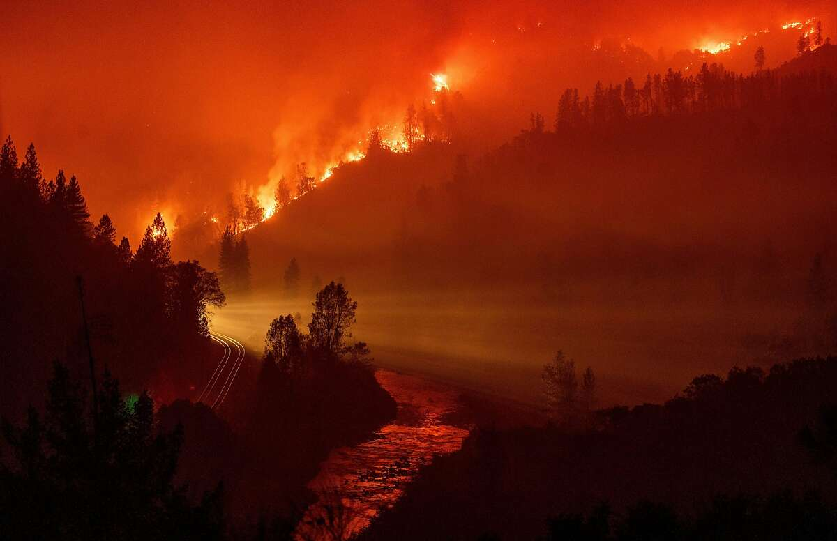 TOPSHOT - Light from a train is seen as it rounds a bend near the Sacramento River as flames from the Delta Fire fill a valley in Delta, California on September 6, 2018. (Photo by JOSH EDELSON / AFP) (Photo credit should read JOSH EDELSON/AFP/Getty Images) *** BESTPIX ***