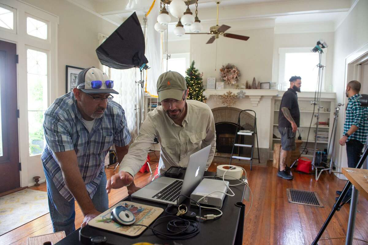 HEB art director Ronnie Arredondo and photographer Rusty Bradford scrutinizes test images during a shoot in the empty Monte Vista house of Alicia Mendez.