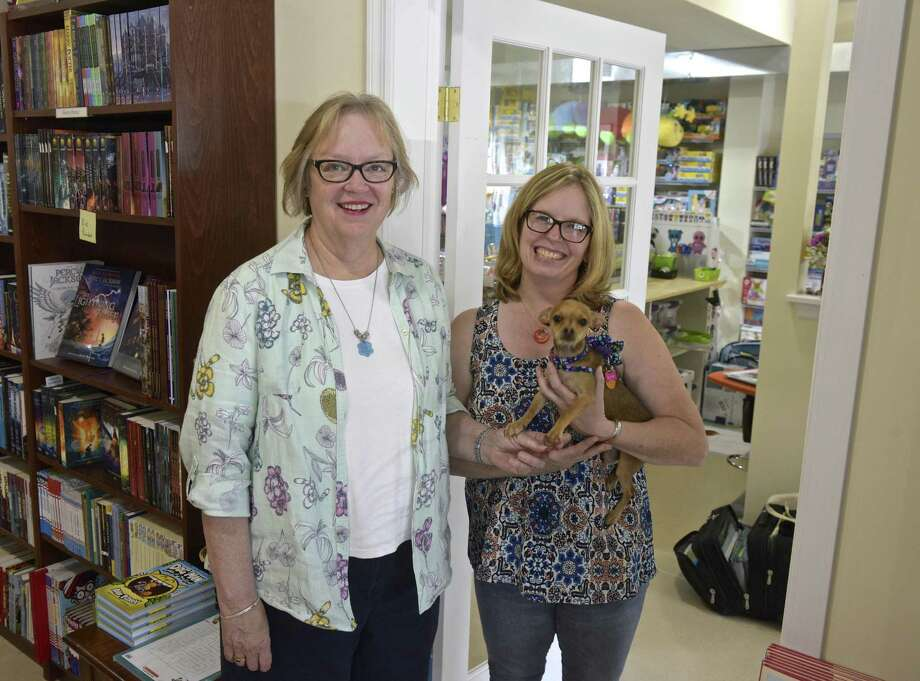 Alice Hutchinson, left, owner of Byrds Books, and Kimberly Ramsey, with Josie, owner of The Toy Room, both moved to new locations in Bethel, right next door to each other in a downtown building rebuilt after a fire last year. they had a door installed between the stores. Wednesday, September 5, 2018, in Bethel, Conn. Photo: H John Voorhees III / Hearst Connecticut Media / The News-Times