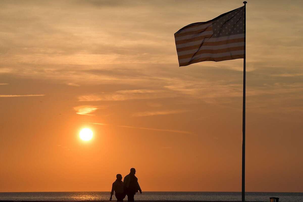 People pass by an American flag on the beach on September 3, 2018 during the 44th Deauville US Film Festival of Deauville. (Photo by LOIC VENANCE / AFP)LOIC VENANCE/AFP/Getty Images