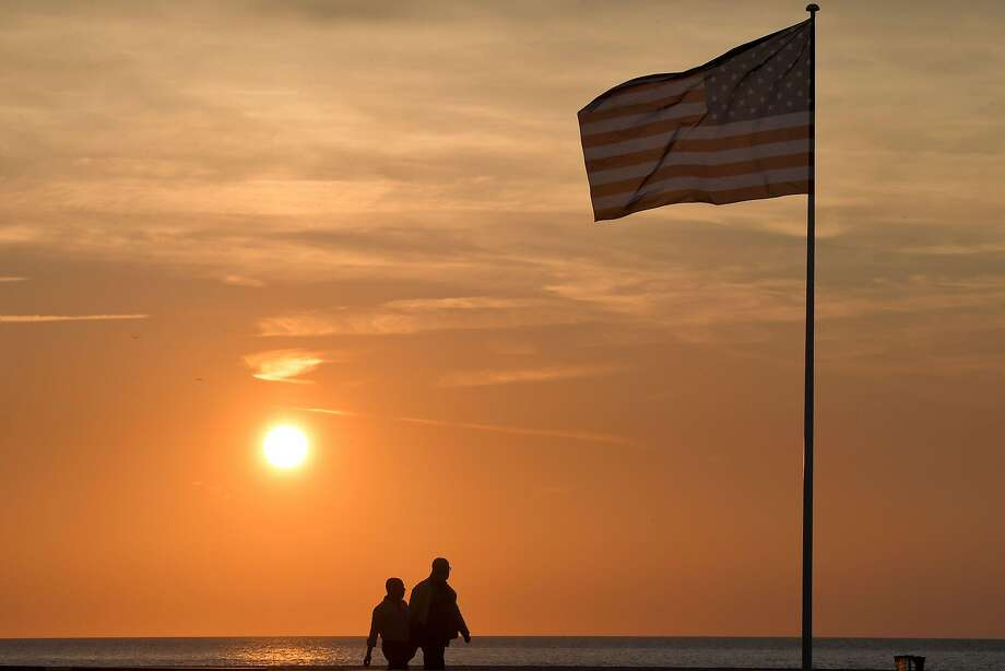 People pass by an American flag on the beach on Monday during the 44th Deauville U.S Film Festival in France. Photo: LOIC VENANCE;Loic Venance / AFP / Getty Images