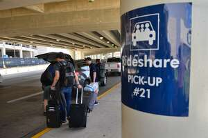 Passenger's get into a vehicle at the Rideshare Pick-Up area of the San Antonio International Airport.