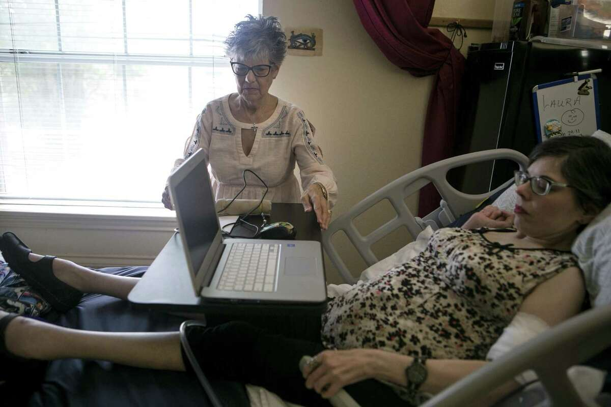 Anita Lunde adjusts her daughter Laura Corso's computer as Corso prepares to show how she writes poetry in her room at Meridian Care. Lunde submitted some of Corso's poetry in a letter to Express-News poetry editor, Jim LaVilla-Havelin. He chose the poem