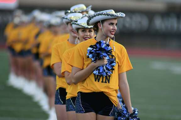 """Captain Lauren Lackey, from right, a junior, and Brooke Rogers, a freshman, and the Kingwood Fillies, stand in formatiion for the playing of the National Anthem before kickoff of the Mustang's football season home opener versus Dekaney at Turner Stadium in Humble on Sept. 6, 2018. The gold shirts, worn by the Fillies and KHS students, parents and fans, were printed with """"Gold...Fight...Win"""" (Fighting Childhood Cencer Together) to represent the mantra of the school's fundraiser in support of Addi's Faith Foundation, Mothers Against Cancer and the L3 Foundation."""