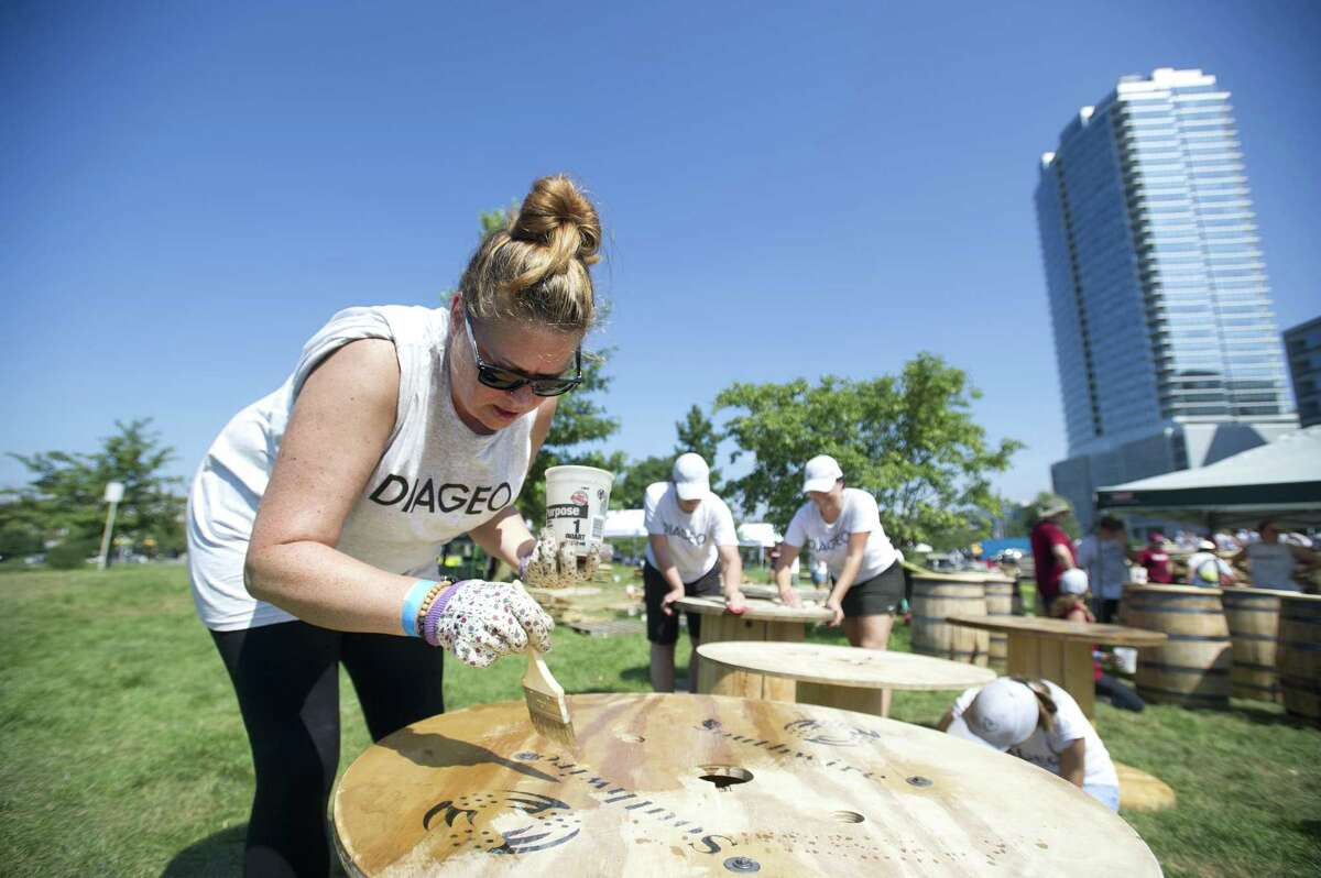 Diageo employee Bridget Connolly, of Norwalk, stains a spool table while volunteering to help build the Back Porch at Mill River Park in downtown Stamford, Conn. on Wednesday, Sept. 5, 2018. The Back Porch is set to be an all-season community space and will include a dog run, beer garden, bocce courts, fire pits and a children's play zone.