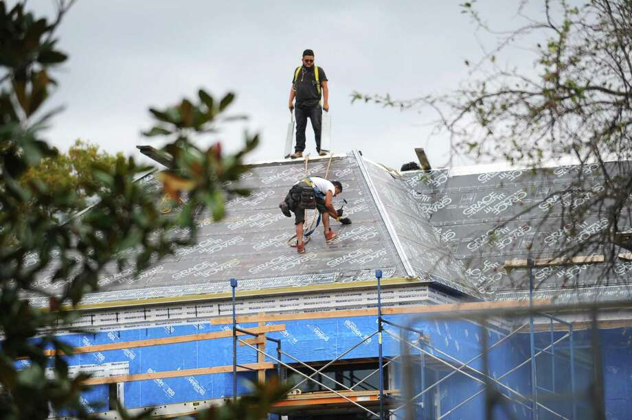 Construction workers roof a new house in October 2017 in Greenwich, Conn. Photo: Michael Cummo / Hearst Connecticut Media / Stamford Advocate
