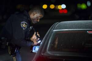 Harris County Precinct 8 deputy constable Jonathan Toliver talks to a motorist during a traffic stop on the Gulf Freeway Service Road.