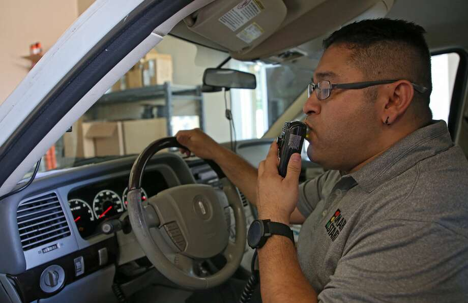 Smart Start assistant manager Omar Hernandez blows into the ignition interlock system to make sure the device works properly. Photo: Godofredo A. Vasquez/Staff Photographer