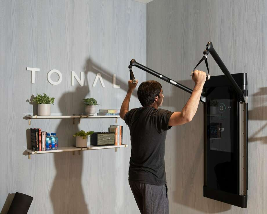 Nate Bosshard, chief marketing officer of Tonal, works out on the startup's wall-mounted machine. Its electromagnetic weights and cables create an experience that does not rely on plates, barbells and gravity. Photo: Photos By Cayce Clifford / New York Times