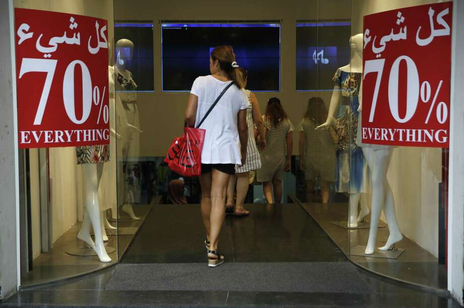 In this Monday Aug. 20, 2018 photo, a clothes shop offers big discounts, in Beirut, Lebanon. Nearly four months after Lebanon held its first general elections in nine years, politicians are still squabbling over the formation of a new government amid uncertainty over a long stagnating economy, struggling businesses and concerns over the currency. Photo: Hussein Malla /Associated Press / Copyright 2018 The Associated Press. All rights reserved.