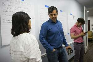 Democrat Sri Preston Kulkarni (center) talks with a supporter in his campaign office on Thursday, Aug. 30, 2018 in Sugar Land. Kulkarni's staff has been running phone banking operations with various volunteers who can speak a diverse group of languages from Mandarin Chinese to Tamil to Spanish. The 22nd Congressional District Kulkarni is running in is considered the most diverse in the state and includes Sugar Land and much of the rest of Fort Bend County.