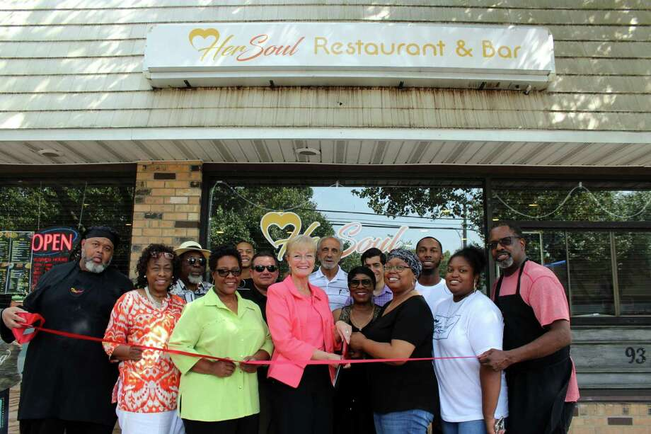 FOOD WITH SOUL: Mayor Nancy R. Rossi, center, cuts the ribbon Aug. 28 with HerSoul owner Karen May to mark the ceremonial opening of the new soul food restaurant and bar at 93 Campbell Ave., formerly Peroles Restaurant & Bar. Joining the celebration are, from left, chef Howard Smith; customers Jackie Smith-Wright and Ernest McIver; Councilwoman Robbin Watt Hamilton, D-5; May's nephew Chrishaun Goins; Fred A. Messore, city commissioner of planning and development; mayoral Executive Assistant Lou Esposito; customer Carroll E. Brown; state Rep. Michael A. DiMassa, D-West Haven; and May's son, Justin, daughter, Ashley, and husband, Steven. The family-style restaurant specializes in steaks, barbecue ribs, burgers, fried chicken, ceviche, including red snapper, and other popular Southern dishes, which are prepared by Smith and chef Andre Browning. HerSoul is open Sunday, noon-8:30 p.m.; Tuesday, 1-8:30 p.m.; and Wednesday-Saturday, 11 a.m.-10 p.m. Photo: Contributed Photo / Michael P. Walsh - City Of West Haven