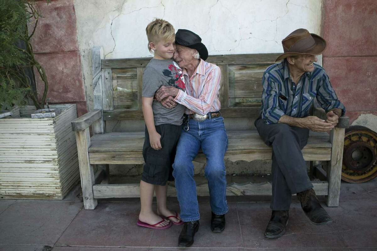 Nita Brashear affectionately squeezes Baiyley Baker, 9, as she sits with her partner Ray Masseau on the porch of the Starlight Theatre in Terlingua, Texas, Thursday, Aug. 30, 2018.
