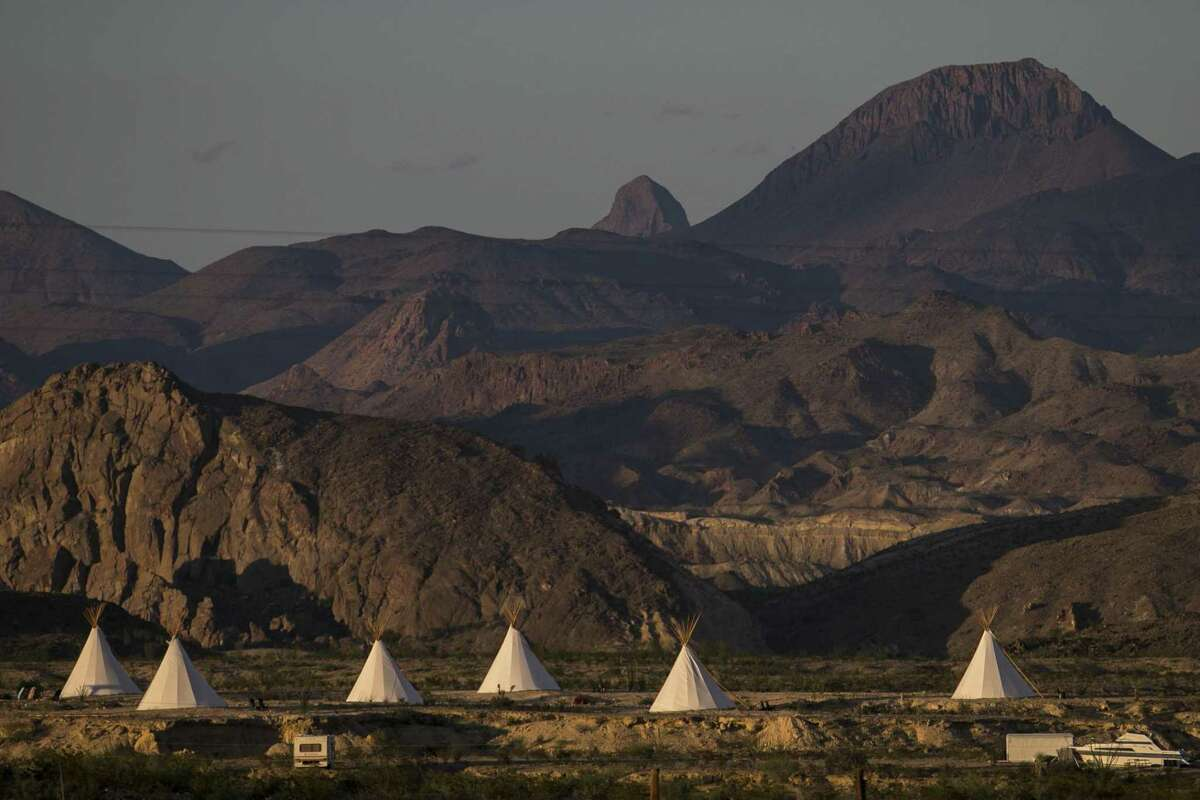 The sun sets on the Basecamp Terlingua tipis in Terlingua, Texas, with the Chisos Mountains in the background Thursday, Aug. 30, 2018. The tipis are owned by Jeff Leach, who has built a handful of nightly rentals around Terlingua and has the locals concerned. Nightly rentals and sky rocketing land prices has created a housing crisis in Terlingua.