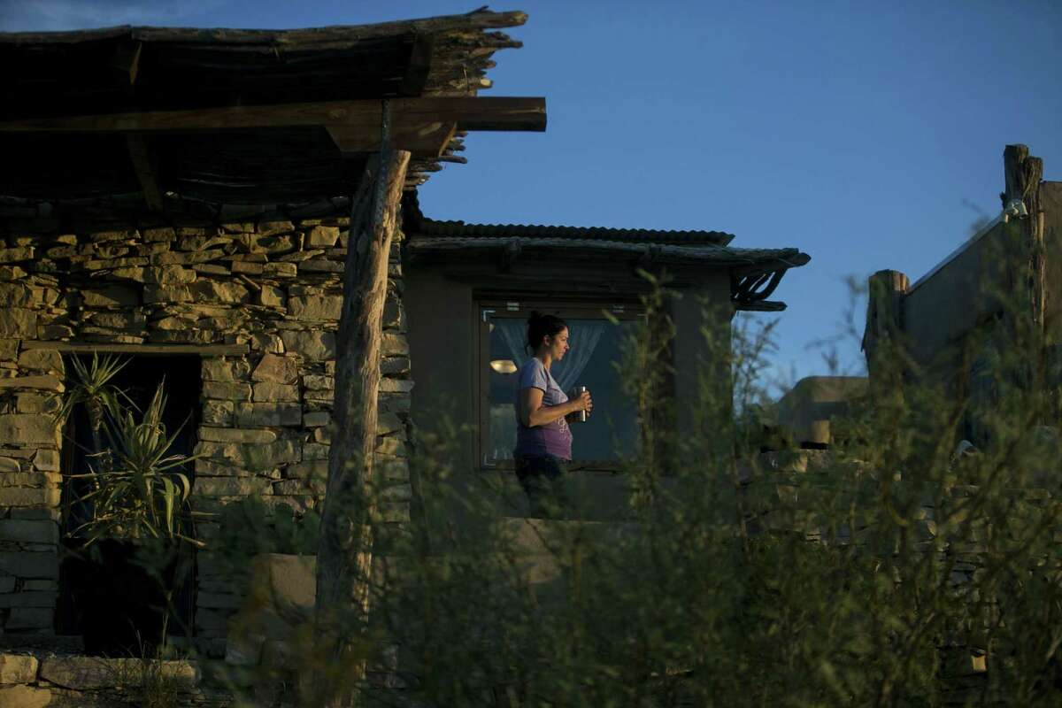 Tenaya Lofts of Okla., walks out onto the porch of the Airnb she and her husband Tye (not pictured) rented in the Terlingua, as the sun rises Thursday, Aug. 30, 2018. The newlywed's visit to Terlingua is part of their honeymoon trip to the Grand Canyon.