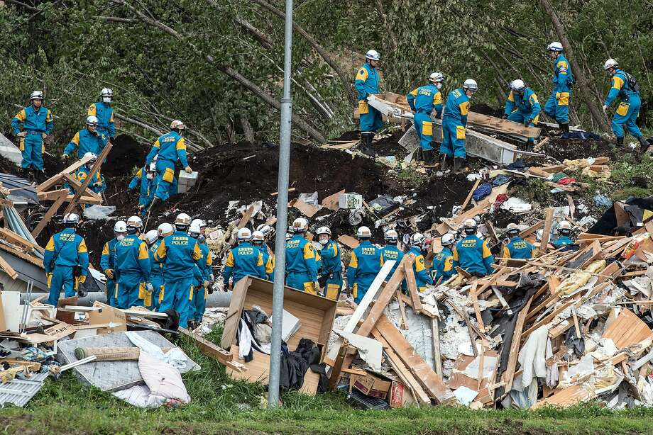 Rescue workers search through the rubble of a building that was destroyed by a landslide caused by a 6.7-magnitude earthquake in Atsuma, Japan, about 40 miles southeast of Sapporo. Photo: Carl Court / Getty Images