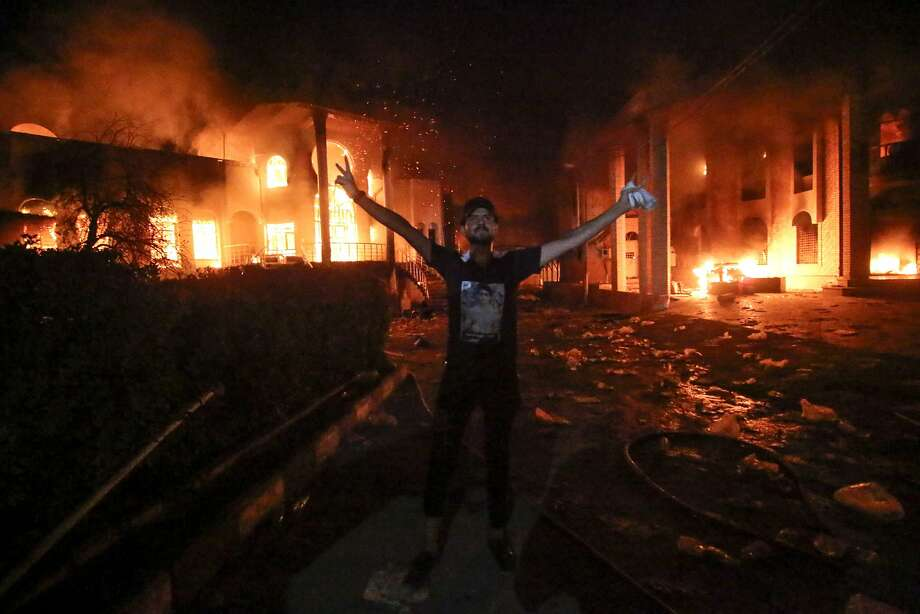 An Iraqi man flashes the victory sign after angry protesters set fires inside the Iranian consulate in the southern port city of Basra. Photo: Haidar Mohammed Ali / AFP / Getty Images