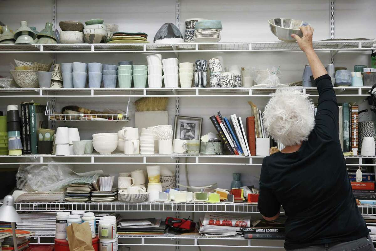 Sculptor Tracye Wear reaches for a bowl with different glazes on it in her Heights studio.