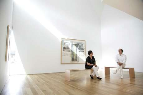 Surpik Angelini, left, and architect Troy Schaum bask in the morning light of the Transart Foundation building's intentionally spare front room, in front of a large work by Robert Rauschenberg.