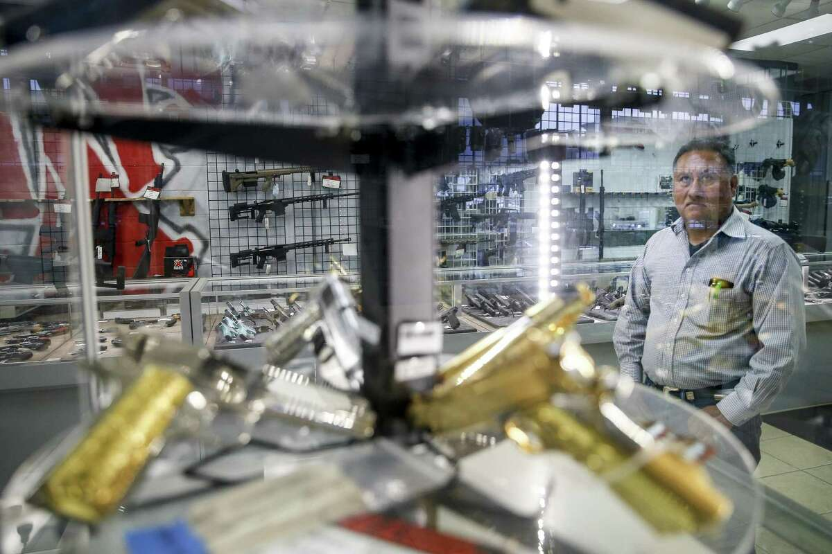 A customer, who wished to not give his name, looks at a case of handguns at Full Armor Firearms Thursday Sept. 6, 2018 in Houston. After demand for firearms reached record highs on the night of the 2016 election, sales have fallen off sharply in what manufacturers are calling the Trump slump.