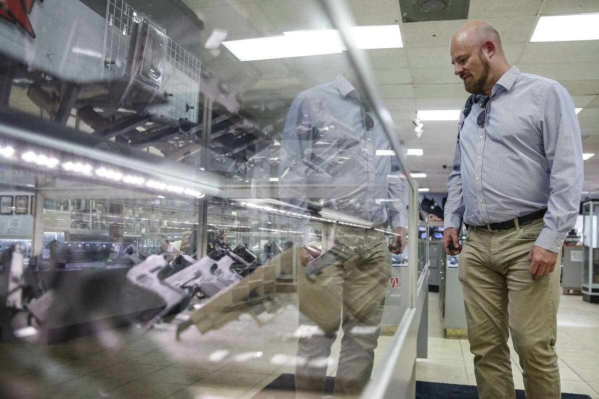 Dave Thompson, from the UK, looks at a case full of handguns at Full Armor Firearms Thursday Sept. 6, 2018 in Houston. After demand for firearms reached record highs on the night of the 2016 election, sales have fallen off sharply in what manufacturers are calling the Trump slump.