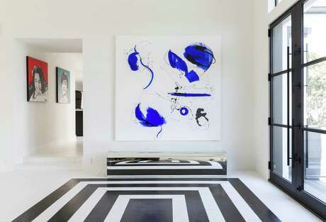 Modern art is posted at the entrance of the Memorial home of interior designer Nina Magon and her husband, builder Karun Magon.