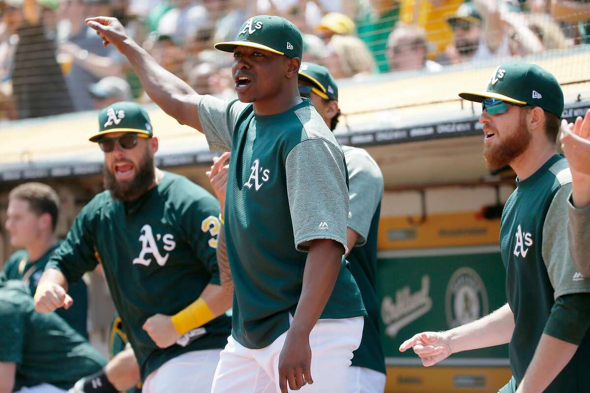 Oakland Athletics Jharel Cotton cheers as A's Khris Davis (2) doubles on a line drive to left field to score Marcus Semien and Jed Lowrie during the first inning of an MLB game between the Oakland Athletics and Houston Astros at the Oakland�Alameda County Coliseum on Saturday, Aug. 18, 2018, in Oakland, Calif.