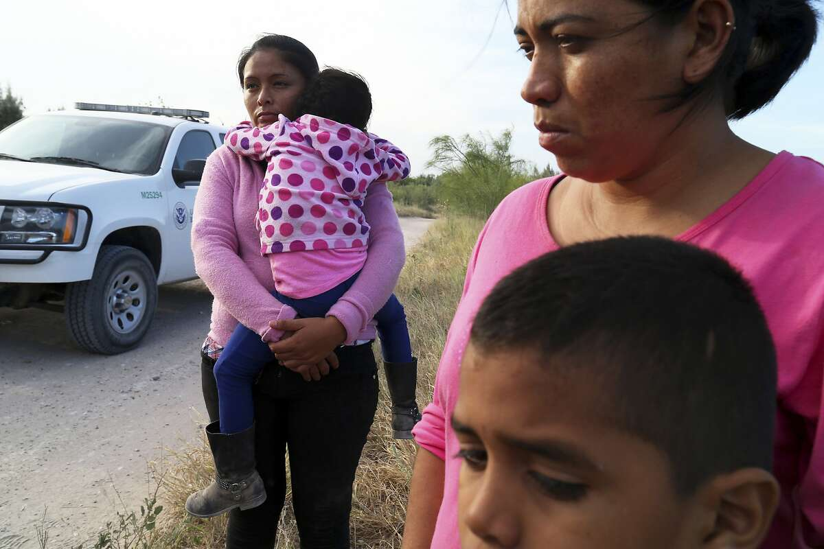 Border Patrol agents process a group of migrants from Honduras and Guatemala, mostly women and children, found walking near the Rio Grande near McAllen, Texas, June 18, 2014. Stepping up efforts to reduce the influx of illegal Central American migrants, the Obama administration announced plans Friday to detain more of them and speed up the deportation process. (Jennifer Whitney/The New York Times)