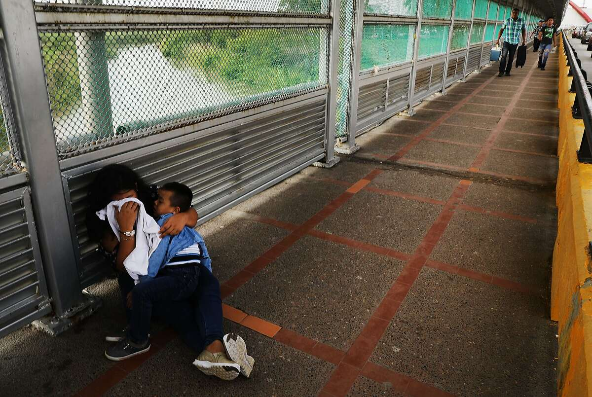 A crying Honduran woman and her child wait along the border bridge after being denied into the Texas city of Brownsville which has become dependent on the daily crossing into and out of Mexico on June 22, 2018 in Brownsville, Texas. Immigration has once again been put in the spotlight as Democrats and Republicans spar over the detention of children and families seeking asylum at the border. Before President Donald Trump signed an executive order Wednesday that halts the practice of separating families who were seeking asylum, over 2,300 immigrant children had been separated from their parents in the zero-tolerance policy for border crossers. (Photo by Spencer Platt/Getty Images)