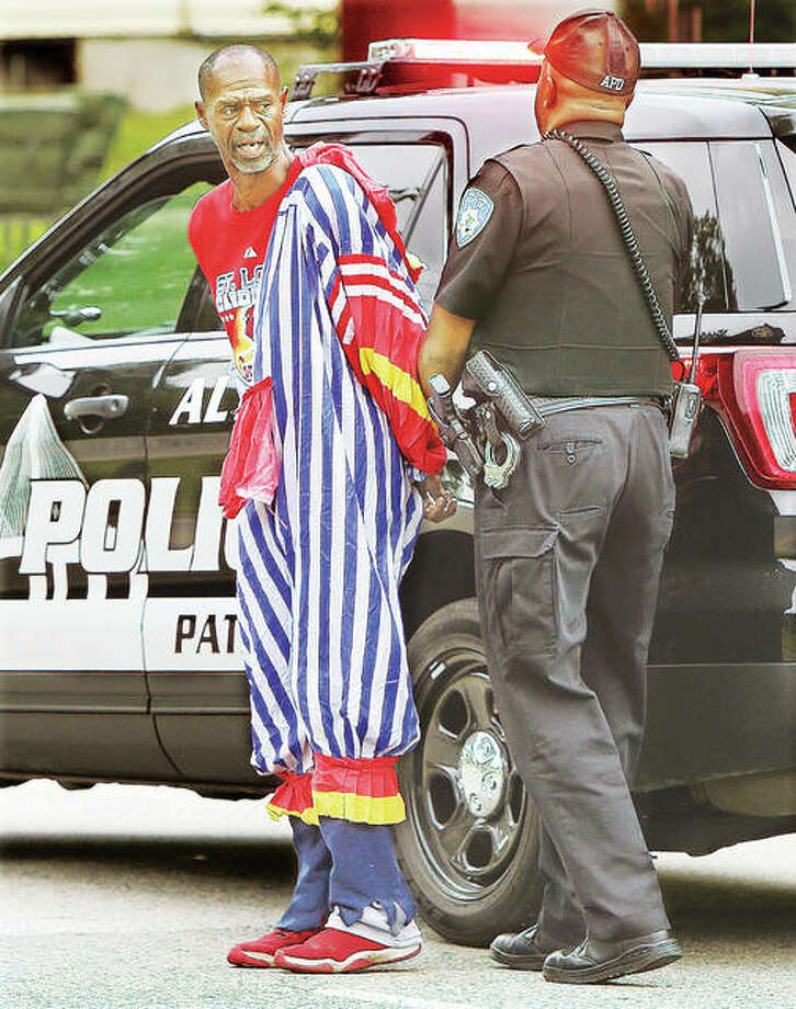 Alton Police officer Tony Bumpers, right, escorts Ronald M. Singleton, 54, to a police car Friday with Singleton dressed in a clown costume and yelling obscenities at another officer following his arrest on Washington Avenue. Singleton was reported allegedly kicking on the door of a vacant business in the 2500 block of Washington Avenue while dressed as the clown. Photo: John Badman | The Telegraph
