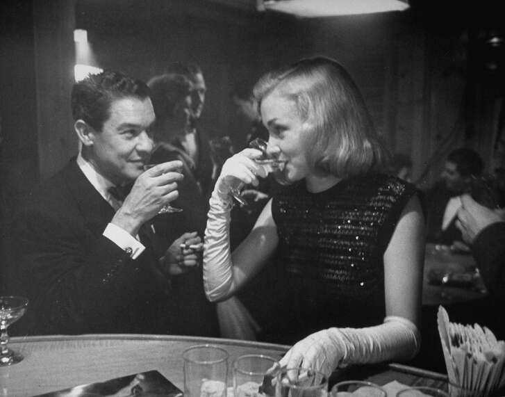 Nina Foch and dress designer Jean Louis sip champagne at Samuel Spiegle's New Year's Eve party, 1949.
