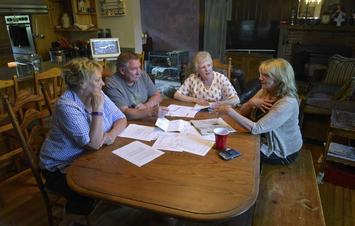 Neighbors Cheryl and Arthur DePoi, left, Barbara Murphy and Laura Staffieri, right, talk around the DePoi's kitchen table. Some residents near Huckleberry Hill Elementary School are having a problem with salt in their wells. Thursday, August 30, 2018, in Brookfield, Conn.