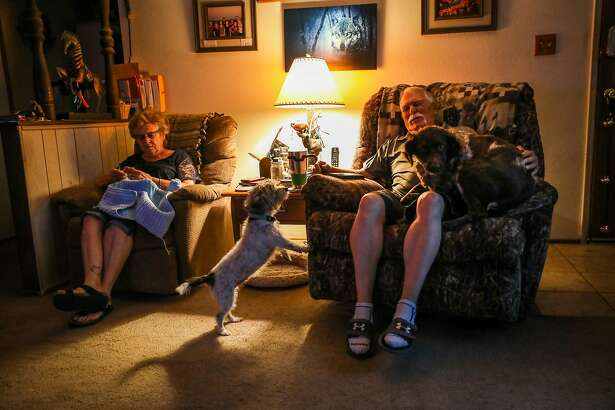Ted Hickman (right) and wife Linda Hickman relax with their dogs Toto (center) and Lady (right) at their home in Dixon, California, on Monday, Aug. 20, 2018.