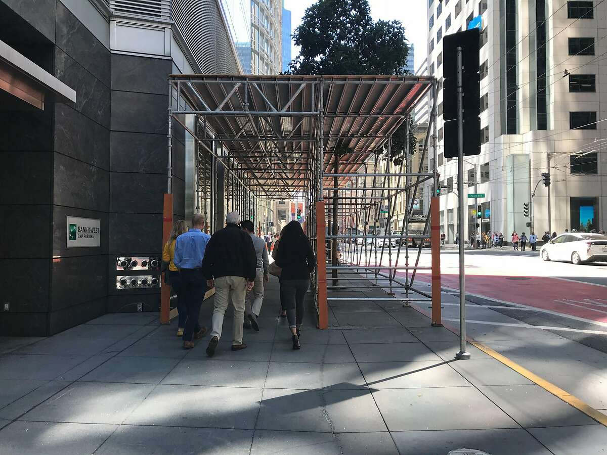 Pedestrians walk beneath a scaffolding constructed in front of the lobby entrance to the Millennium Tower at 301 Mission Street on Friday, Sept. 7, 2018 in San Francisco, Calif. City building inspectors are investigating reports that a window on the 36th floor of the residential tower has cracked and fears were expressed that the window could shatter, raining lethal glass shards down on passers-by at street level.