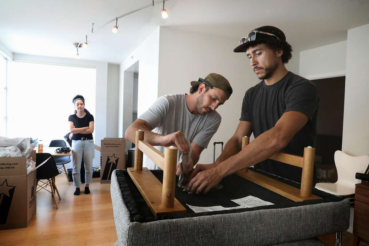 Delivery leads Jake Gonen (middle) and Chris Ledet (right) deliver a couch from Feather to the new apartment of Yuka Ohishi (left) as she watches them put together the couch at her home on Thursday, Aug. 23, 2018 in San Francisco, Calif. SF startup Feather rents household furniture to people on a subscription plan.