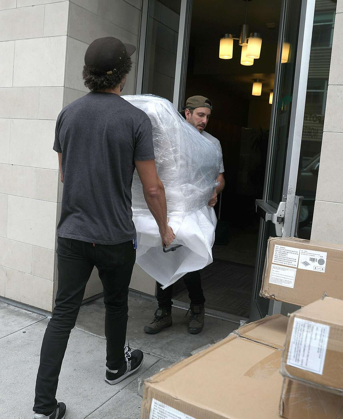 Delivery leads Chris Ledet (left) and Jake Gonen (middle) move household furniture from Feather to an apartment on Kansas St. on Thursday, Aug. 23, 2018 in San Francisco, Calif. SF startup Feather rents household furniture to people on a subscription plan.