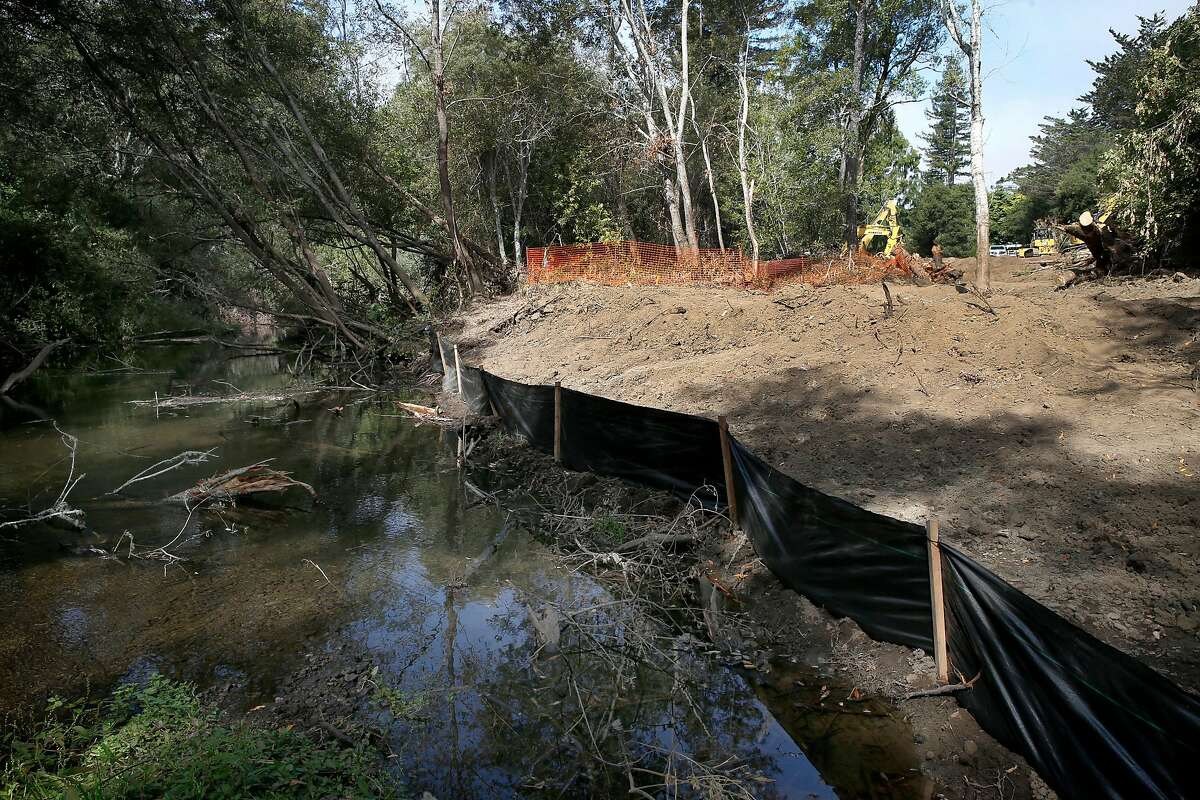 Water in Lagunitas Creek flows past a site where a manmade flood plain channel is under construcion (right) in Olema, Calif. on Wednesday, Sept. 5, 2018. The project removes more than 13,000 cubic yards of dirt and abandoned buildings creating side channels along a one-mile stretch of the creek that will become a refuge for young trout and salmon.