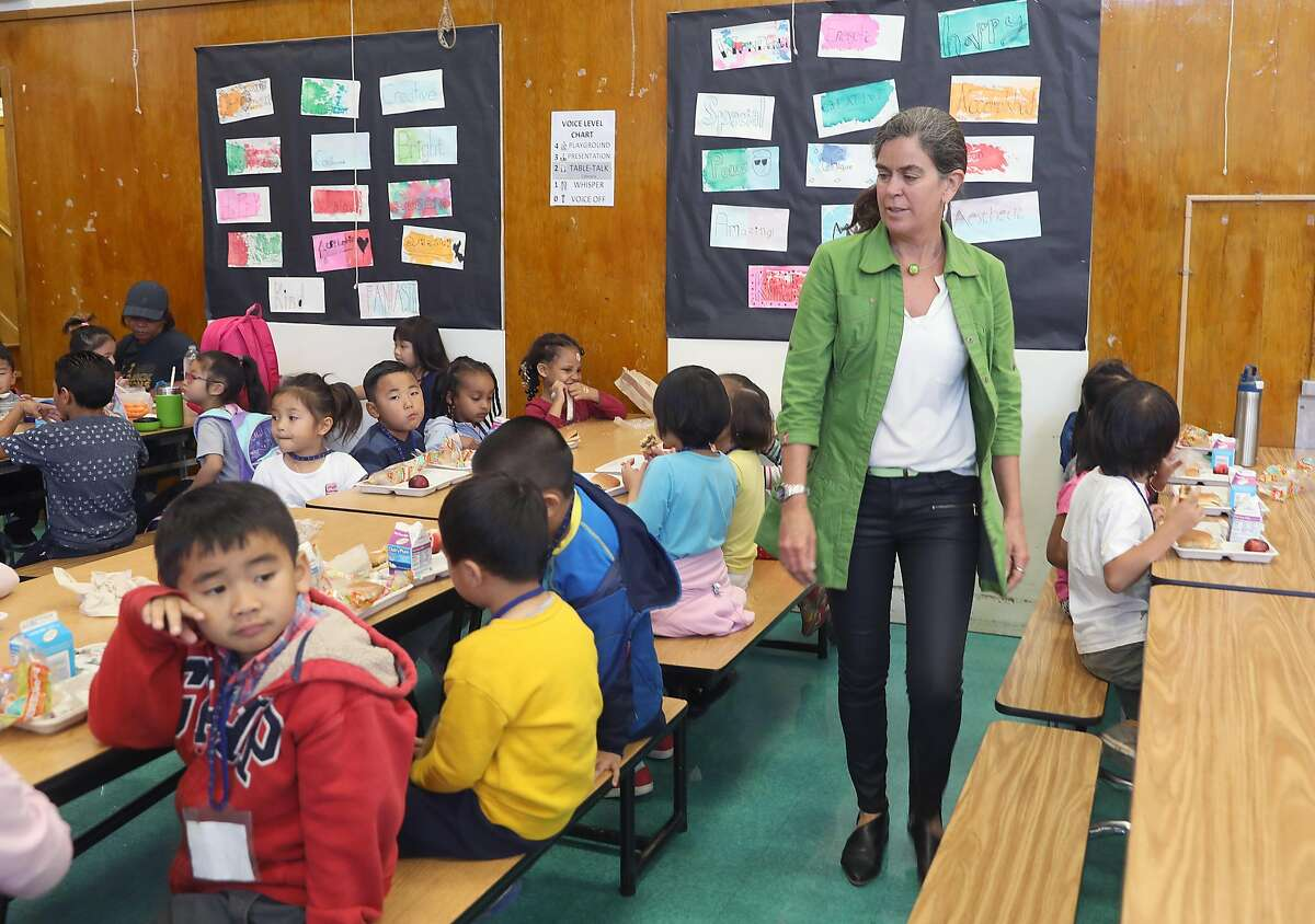 Principal Ingrid Seyer-Ochi checks on her kindergarten students as they have lunch in the cafeteria at Franklin Elementary school on Friday, Sept. 7, 2018, in Oakland, Calif. The after school supper program at Franklin Elementary school has been cut.