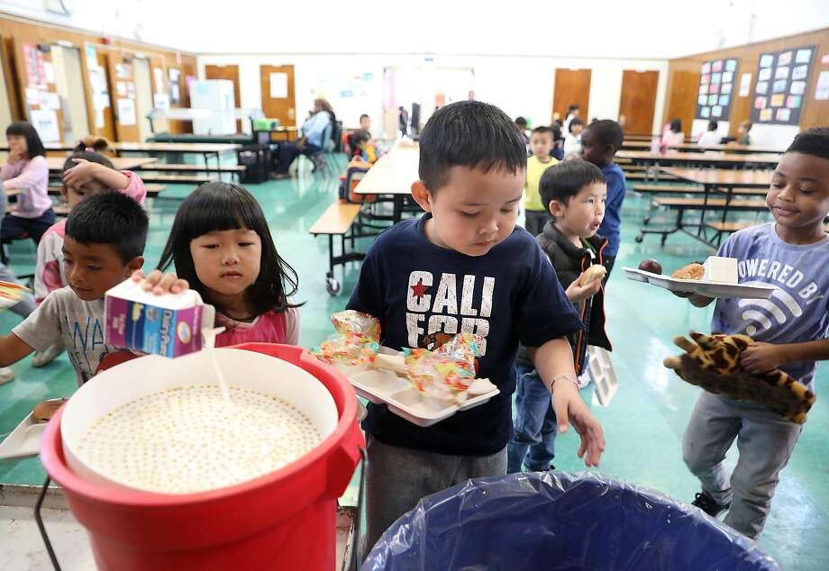 Kindergartner Quan Huu Nguyen (middle) disposes of trash after lunch in the cafeteria at Oakland's Franklin Elementary School. Measure AA would fund early childhood education. Photo: Liz Hafalia / The Chronicle 2018
