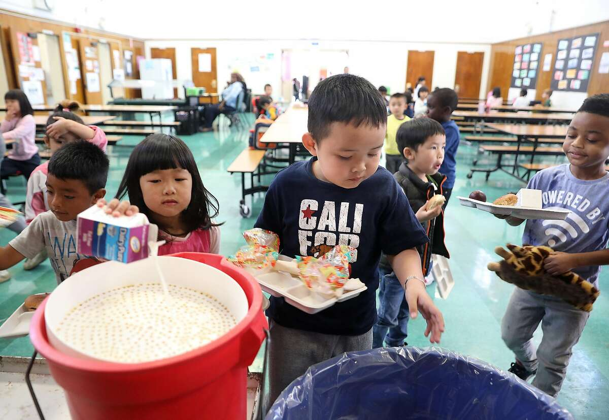 Kindergarten student Quan Huu Nguyen (middle), 5 years old, recycles leftovers after having lunch in the cafeteria at Franklin Elementary school on Friday, Sept. 7, 2018, in Oakland, Calif. The after school supper program at Franklin Elementary school has been cut.