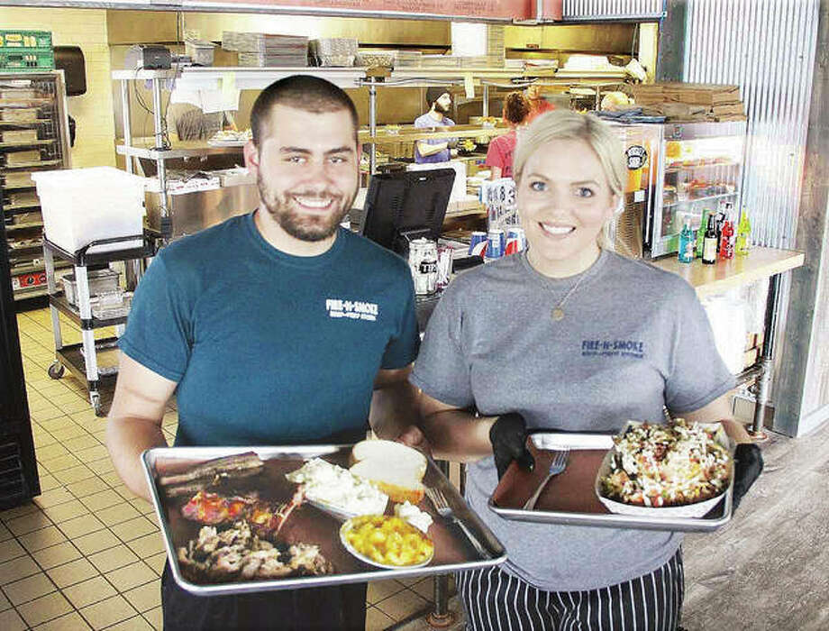 Co-owners James Dooley and Alyssa Edwards hold several items from the menu at Fire-N-Smoke, a new barbecue restaurant in Wood River. The restaurant, at 1800 Vaughn Road, has been very busy since opening about one month ago. Photo: Scott Cousins|The Telegraph