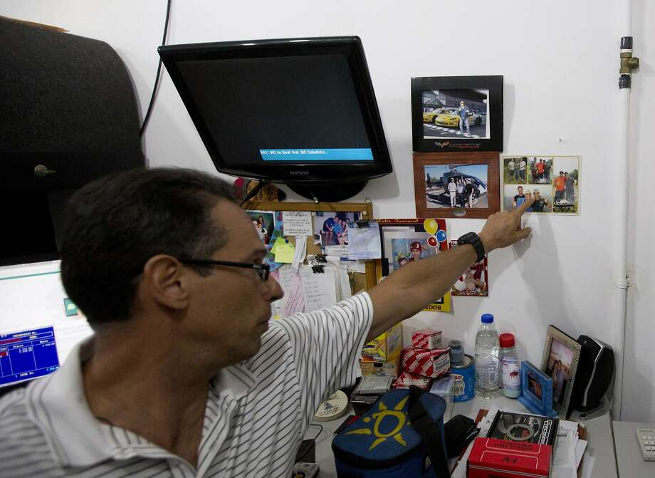 David David points at a photo of his brother, Franklin, last week in his office in Santa Teresa Del Tuy near Caracas. Franklin David was arrested for allegedly raising prices too much. Photo: Fernando Llano / Associated Press