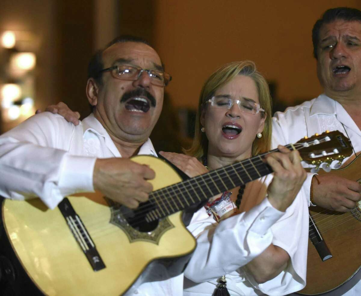 """Carmen Yulin Cruz Soto, mayor of San Juan, Puerto Rico, sings with Antonio Rodriguez, left, of the group """"El Trio Mio"""" at the San Antonio Association of Hispanic Journalists annual gala on Aug. 11. Soto became internationally known for her criticism of President Trump after Hurricane Maria ravaged wide swaths of Puerto Rico, leaving many on the island without power for months on end."""